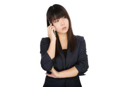 忙しいと電話する女性